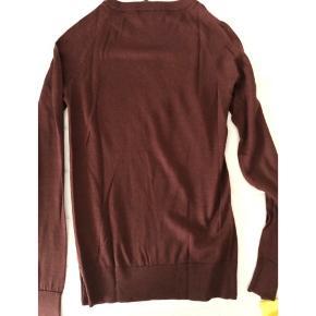 Lækker mørk bordeaux bluse i uld. Det er en tynd strik. Kun brugt en enkelt gang.
