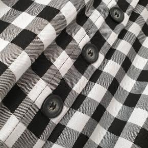 Sort-hvid ternet nederdel fra H&M, 75 cm lang, lukkes med knapper, slids foran og i siderne.  Prisen er ekskl. forsendelse.