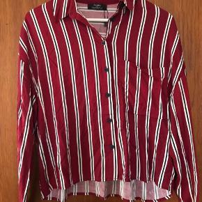 Sød stribet skjorte. Længere bagpå end foran.