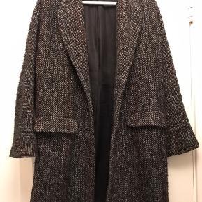 Fed boucle agtig jakke fra Zara. Str. small men passer en 36 og lille 38.  Den er i sorte og lyse nister og en rød tråd ned gennem.  Brugt men i pæn stand.  Køber betaler Porto.