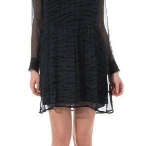 Smuk og sexet kjole i mørkeblå med sort print fra Ganni. Den fine kjole har et flot snit med høj hals og et fint skørt. Kjolens overdel og ærmer er i et gennemsigtigt materiale, hvorimod skørtet har et underskørt som gør at denne del ikke er gennemsigtig