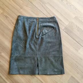 Varetype: Skind nederdel  Farve: Grå   Super flot  nederdel i lækkert skind. Jeg har så meget og får den bare ikke brugt.  ☺️