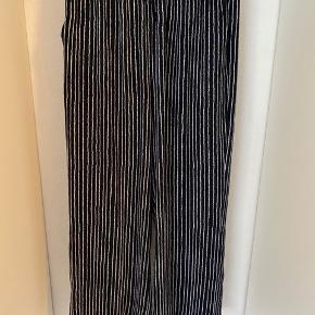 Blå og hvid stribet løse bukser med elastik kant. Fremstår som nye. Vidde ved buksebenene. Luftig og let materiale 💙