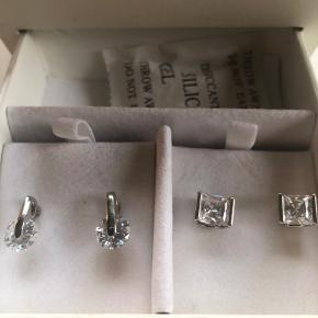 Flot smukkest fra Pierre Cardin i smykkeboks. Består af to par ørestikker og en matchende halskæde. Der har været ur til sættet men det følger ikke med.