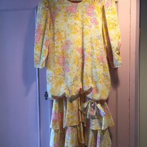 Vintage kjole købt i Sydamerika  Flot stand - dejlig sommergul med lyserøde blomster. Sjovt snit og sløjfe. Passer str L eller XL cirka