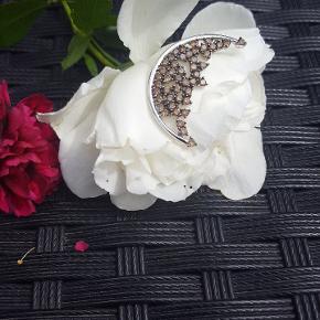 Måne i 14 karat hvidguld med mesterstempel.  46 chokolade- og champagne brillianter.  Vedhæng til halskæde eller evt. designersnor fra Ole Lynggaard. Velholdt! Bud ønskes ikke. Dette er et unika smykke. Passer flot med stjerne øreringe og/eller sølv eller hvidguldskæde. Vurderet til 3000 - 5000 kr. af Lauritz. Beskrivelse af smykket fra Laurits haves.