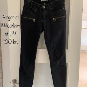 """Flotte lavtaljede jeans med guld-detaljer. Det er en 7/8 dels buks.   Har en """"slidt"""" sort vask.  Fejler ingenting."""