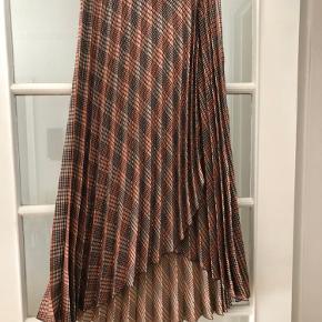 Nederdel aldrig brugt. Fitter en str 36. Med slis og ternet mønster.