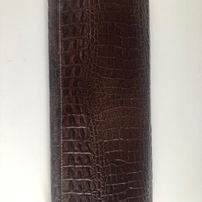 Super fin og elegant vintage clutch/pung. Der er slid i det ene hjørne men fejler ellers intet.  Nypris: 900,-  Mål: 25,5x8 cm