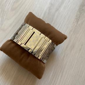 Gucci Twirl ur - model YA112418. Fra 2009. Brugt få gange. Skal have nyt batteri. Selve viser delen kan vendes, så uret kan bruges som armbånd. Se billeder. Fået i gave. Købt hos Klitgaard i Aalborg, som har skrevet modelnummer samt stemplet bogen, som ses på billedet.