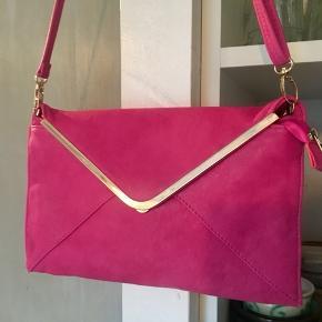 Taske i ægte læder i pink og guldbesætninger. Der er en clutch rem til. Bagpå tasken er der streger fra en pen, hvilket kan ses på et af billederne. Den måler 29,5cm i bredden og er 18cm høj.  Det der er særligt ved denne kuvert taske er at det er ægte læder.