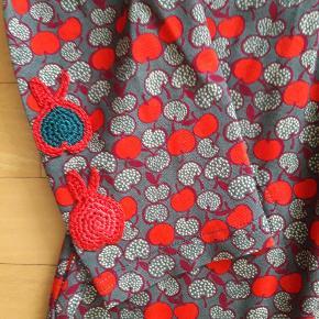 Ny med tags.  Fra røgfrit hjem.  Kjolen hedder Alminas Paradise Apples. Viscose og elastan.  Hæklede æbler nederst på ærmerne. Lommer i sidesømmen.  Længde målt fra skulder 98 cm.  Måler fra ærmegab til ærmegab 46 cm.  Køber betaler porto.