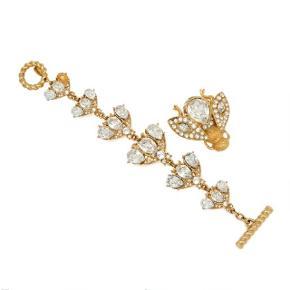 Christian Dior smykkesæt bestående af armbånd og broche af gyldent metal i form af bier, hver prydet med talrige facetslebne klare sten. L. 19 og 5 cm. (2)  Stand: En lille bi i armbåndet mangler en dråbe facetslebet sten.  Sælges samlet