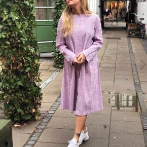 Mads Nørgaard kjole i modellen crinckle pop dupina i farven lilla. Udsolgt i butikkerne. Brugt 1-3 gange og efterfølgende vasket på skånsomt program og med neutral sæbe uden parfume. Ingen tegn på brug, står som ny. Købt i enula9 på Østerbro for fire måneder siden, men har desværre ikke fået den brugt.