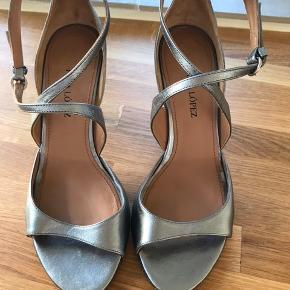Vidunderlige stilletter i model Kanti fra Pura Lopez, str 37 1/2. Brugt 1 gang, men er lige lidt for store. Absolut ingen mærker eller ridser hverken på sko eller hæle (se fotos) Nypris kr 2000.