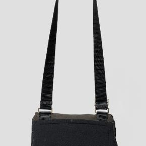 Cool sporty taske fra Prada Sport.  Den er lavet i et lækkert neoprene materiale og er vældig praktisk.   Farven er lidt et miss and hit mellem brown, grå og sort alt efter lyset.   Der er monteret to ekstra velcro pads for ekstra lukke-evne.   Højde: 22 cm Bredde: 30 cm Dybde: 8 cm