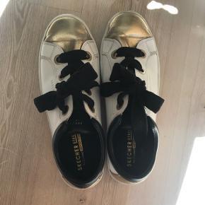 Fede sketchers sko hvide, guld og sorte. Brugt 4 gange ca. Så er i god stand, med en Memory Foam sål. Som gør dem ekstra gode at gå i. Nypris 600kr byd.