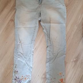 Fede jeans med blomster op ad benene. Er med stræk. Livvidde 108 cm Indvendig benlængde 78 cm Er brugt få gange, så pæne som ny.  BYD gerne - Kig forbi mine andre annoncer og spar penge - også på portoen 😉