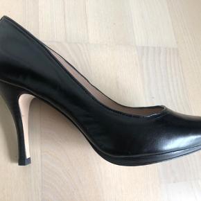 Nye stiletter i sort læder med lille plateau foran. Hælhøjde 7 cm.