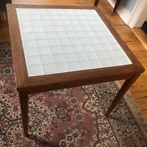 Sælger mit sofabord i teaktræ med matte hvide klinker på overfladen. Har købt bordet genbrugt og selv lagt klinkerne i. Ingen skader eller fejl☺️