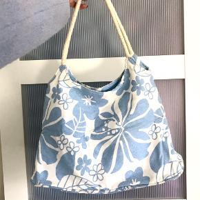 Vintage skuldertaske i lyseblåt og hvidt blomstermønster. Der medfølger en lille pung i samme mønster 🤍🧊  Jeg sender meget gerne flere billeder 😄