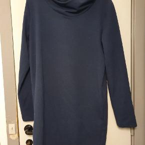 Smuk anorakinspireret kjole fra den grønlandske designer Bibi Chemnitz. Kjolen er i viskose og elastan og har hætte bagpå. Den går til midt på knæet