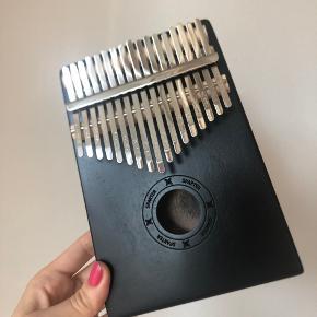 """Kalimba musikinstrument med 17 notespinde. Udført i smukt træ. Spiller de smukkeste toner med tommelfingrene!  Ny i æske. En perfekt anderledes gave.   Kan afhentes på Islands Brygge eller sendes efter ønske 💌  Brug gerne """"Køb Nu"""" 😊"""