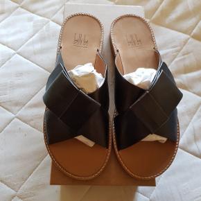 BILLI BI SANDALER STR. 38  Brun slip-in sandal udført i bæredygtigt læder* med rundet snude og lav hæl. Sandalen har to brede krydsende remme henover foden med foldedetalje.  *BiOnature oak leather er bæredygtigt lige fra produktion til produkt. Under hele produktionsprocessen er vandforbrug samt spildevand reduceret til et absolut minimum, så det påvirker miljøet mindst muligt. Læderet er tørret i stuetemperatur og naturligt indfarvet med eg og er derfor både krom- og metalfri.  Skoæske lavet i 100% genbrugskarton.  • Hælhøjde: 2 cm • Ydersål: Hel lædersål • Indersål: Skind • Foring: Skind • Normal i størrelsen