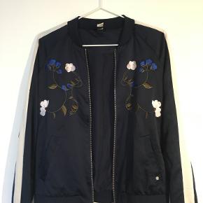 Super smart jakke med et flot broderi. På ærmerne er der en hvid streg hvor der tildels er små snore.