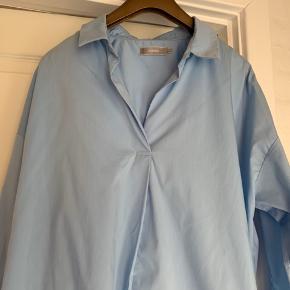 Fin rummelig skjorte lukket foran  78 % polyester  19% polyamid 3%  elestan Brystmål 64 x 2 cm Længde. 69 cm