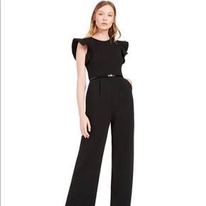 Den fedeste buksedragt fra Calvin Klein med brede ben og tilhørende bælte.  Svarer til en str. 40/L.  Aldrig brugt og fortsat med prismærke.