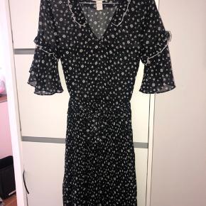 Fin kjole med hvid/grøn blomsterprint, bindebånd i taljen og flæsedetaljer og udskæring  Byd gerne!