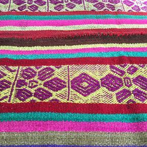 """Disse gulvtæpper eller """"Frazadas""""  er 100% fårulds tekstil, der er håndvævet af Andeskvinderne (Cusco -Peru). De bruges til at beskytte Andes-folket mod frysende temperaturer om vinteren i deres landsbyer, der ligger over 3000m over havets overflade.  Mål: 182x156cm"""