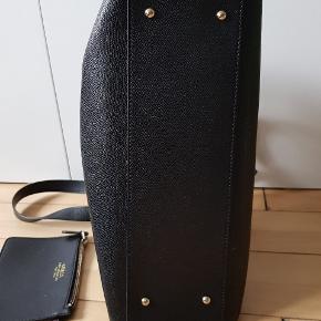 Brugt få gange, og er i perfekt stand! Den kan både bruges som håndtaske, som skuldertaske og som cross-body.  Der er et stort rum, der lukkes med lynlås. Derudover to rum, der lukkes med knap. I den forreste er der tre små lommer nede i, og i den bagerste er der en ekstra lille lomme, der lukkes med lynlås. Der medfølger en lille pung med rem, som kan knappes fast. Kom endelig med et bud!