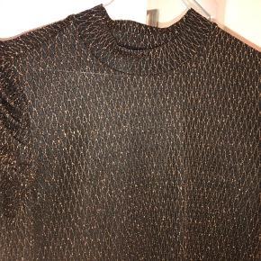 Fin bluse i sort med kobber/guld-tråd i. Lidt pufærmer og halvhøj hals. Brugt en gang.