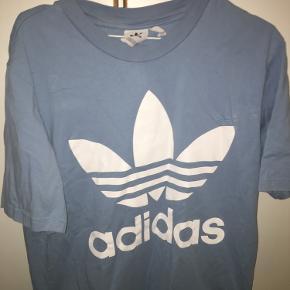 Flot baby blå t shirt fra Adidas  Herre model  Str M Er brugt som oversized look til kvinde  Logoet er intakt