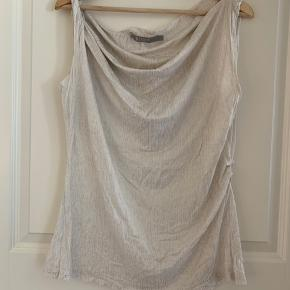 Smuk Tiger of Sweden bluse i hvid med gulddetaljer. Blusen er draperet over brystet, så den falder smukt.  Passer str. M-L, 38/40.