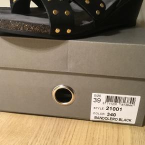 NY Cashott 21001 sandal, black. Str. 39/40  Sandalen er mærket med str. 39. Jeg mener, at den svarer til en str. 40. Den er anvendt en enkelt gang, men desværre for stor til mig. Min vurdering at den er 1 nummer større end normal.  Kom gerne og prøv sandalen. Indvendig længde ca. 26,5 cm