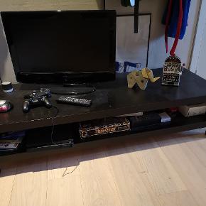 Lang sort tv-bord med enkelte skrammer. 150 cm lang. 55 cm bred. 35 cm høj.