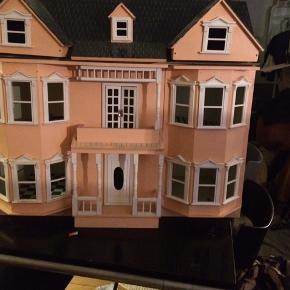 Stort dukkehus i laksefarvet. Det har mangler og brugsspor men stadig fint. Der medfølger lys
