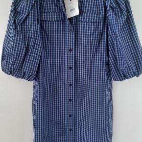 Helt ny kjole fra Second female i str. M, stadig med prismærke. Farven er blå, brun, sort. 100% bomuld. Måler 99 cm i længden.  Nypris 800.-