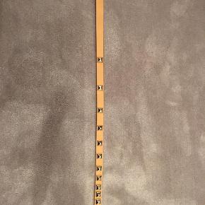 Varetype: Bælte Størrelse: 90cm Farve: Beige  Fint nitte bælte med guld trim. Lyse brun i farven