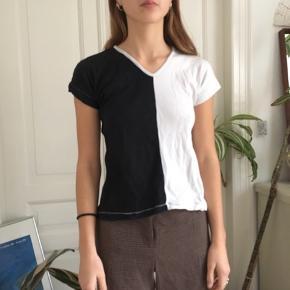 Fed bluse hvor den ene halvdel er sort og den anden hvid. Den er hjemmesyet nogle steder.