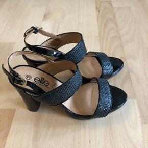 Flotte sko i læder med guldspænder i siden. Hælen er ud af træ og 10 cm høj. De er aldrig brugt men kun prøvet på indenfor.