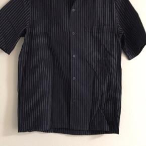 Skjorten har samlet støv da den ikke er blevet brugt i lang tid. Den har ingen slitage, den trænger bare til en vask.