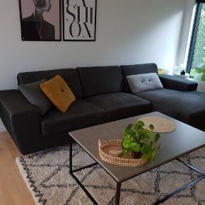 Mørkegrå sofa med chaiselong. Uden pletter, men der er lidt slid på fodenden af chaiselongen (se billede), som evt kan skjules med et tæppe. Skal hentes i Aabybro.