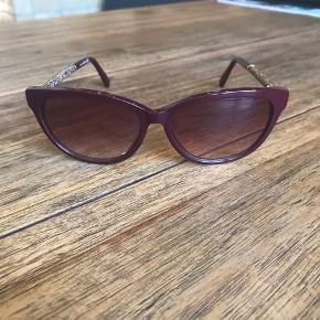 Vinrøde solbriller fra Swarovski med sten på siden. Aldrig brugt. Originalt etui medfølger. Købt i brillebutik i Milano. Oprindelig købspris: 1800kr.