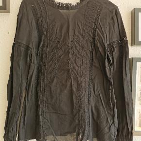 Skjorten er faktisk sort, men for at kunne se detaljerne har jeg øget kontrasten på billedet. Både små flæser, blonder og anglaise pynter skjorten.