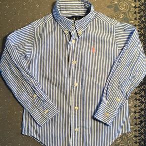 Varetype: Skjorte Farve: Blå Oprindelig købspris: 480 kr. Prisen angivet er inklusiv forsendelse.  Super sød blåstribet skjorte fra Ralph Lauren. Passer til en dreng på 1,5 - 2 år (str. 92)  Brugt 1 gang. Kommer fra røgfrit hjem  Fragt er inkluderet i prisen.