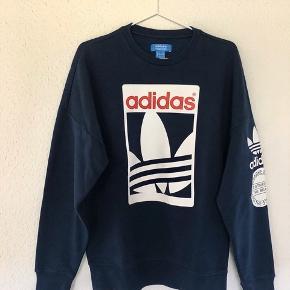 Mørkeblå Adidas sweatshirt i størrelse small Er brugt under 10 gange Den er lidt stor i størrelsen, og kan godt kaldes oversize Den er lavet af 70% bomuld, 30% polyester, og den er så god som ny Sælger den, da jeg aldrig rigtig fik den brugt, og den nu er blevet for lille til mig Kan vaskes i maskine